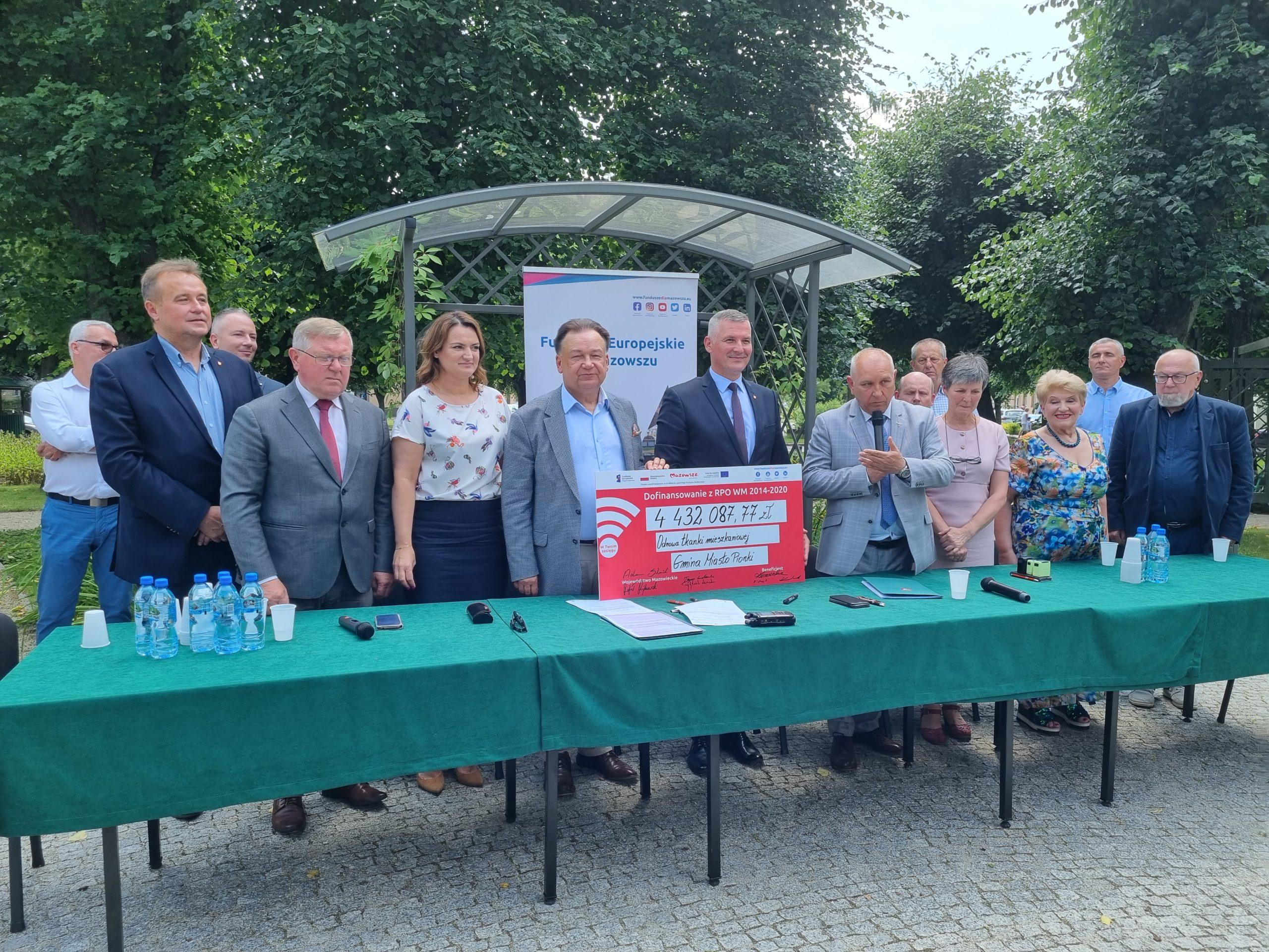 Uczestnicy uroczystego podpisania umowy trzymają symboliczny czek o wartości ponad 4,4 mln zł na odnowę budynków mieszkalnych w Pionkach