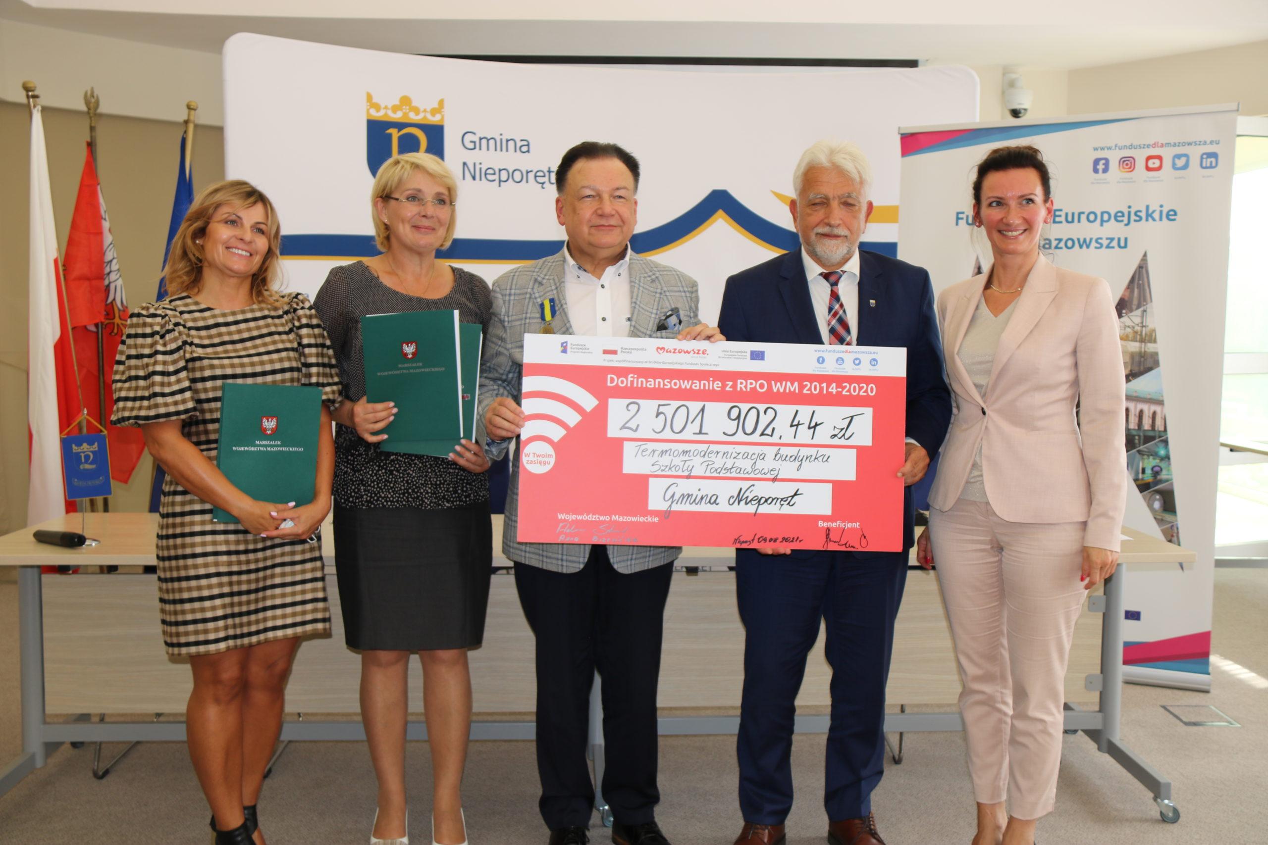 Uczestnicy z pamiątkowym czekiem na kwotę ponad 2,5 mln zł na remont szkoły podstawowej w Stanisławowie Pierwszym